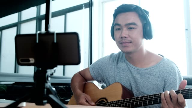 male influencer playing guitar while making video tutorial,vlogger recording guitar lesson on video camera - music stock videos & royalty-free footage