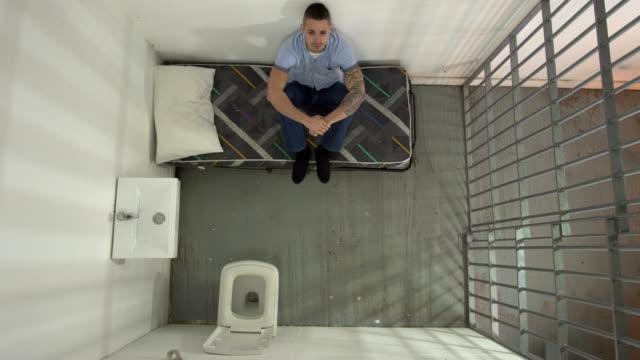 vídeos de stock e filmes b-roll de 4k aerial: male inmate in jail cell sat on bed - cela de prisão
