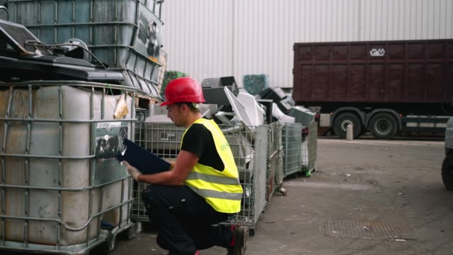 male inspector examining a local waste disposal dump - dump truck stock videos and b-roll footage