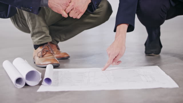 ds male interior architect and female investor pointing out details of the plan set on the floor and having a discussion - flooring stock videos & royalty-free footage