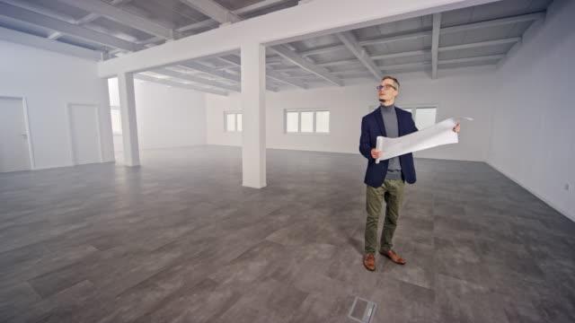 vídeos de stock e filmes b-roll de cs male interior architect looking at the plans walking across the empty office space - área sem divisões