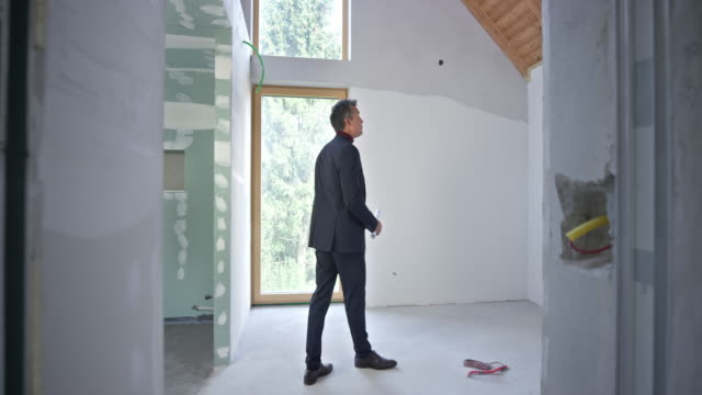 male interior architect standing in the unfinished room and looking at the plans - one man only stock videos & royalty-free footage