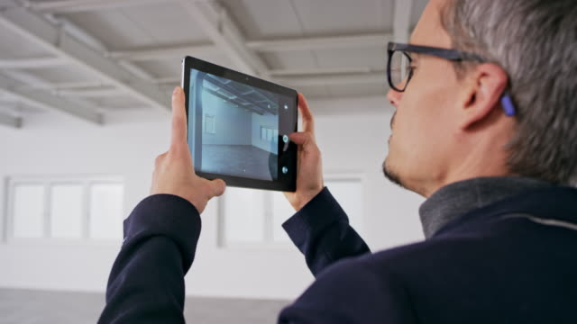 male interior architect taking photos of an empty office space with his digital tablet - architetto video stock e b–roll