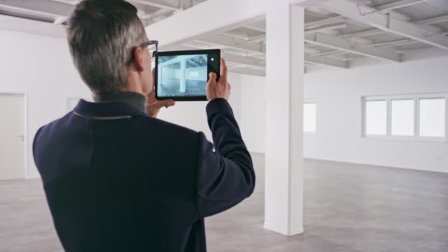 male interior architect taking photos of an office space in an empty business building using his digital tablet - see other clips from this shoot 31 stock videos & royalty-free footage
