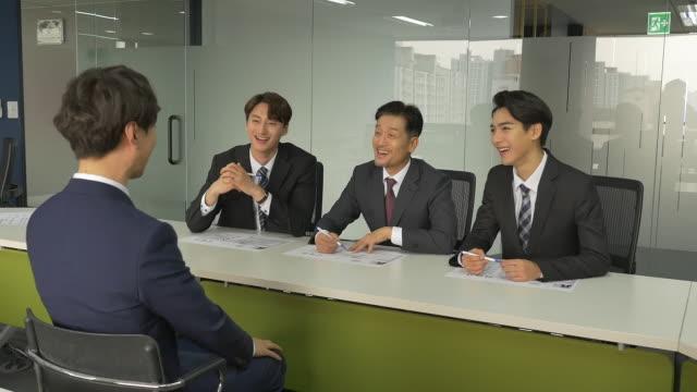 vidéos et rushes de male interviewers conducting an interview with a male job applicant - tenue d'affaires formelle