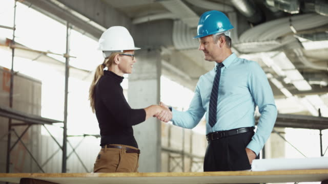 vidéos et rushes de investisseurs ds hommes serrant la main de femme architecte sur le chantier - shirt and tie