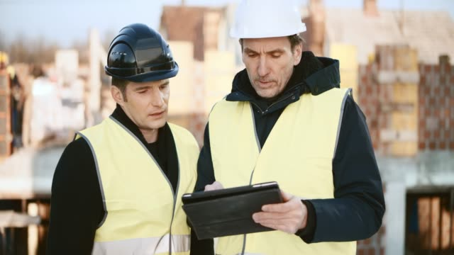male investor talking to the male architect at the construction site while they go over the plans on the digital tablet - blueprint stock videos & royalty-free footage