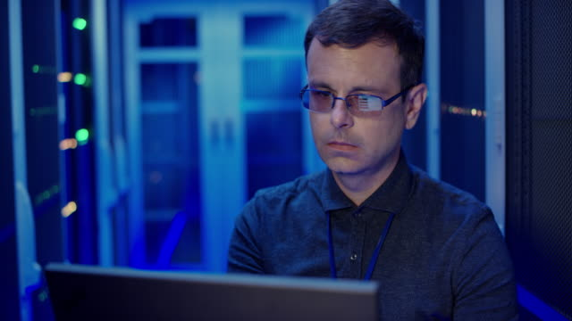 ds male it engineer checking the server operations using his laptop in the server room - navy blue stock videos & royalty-free footage