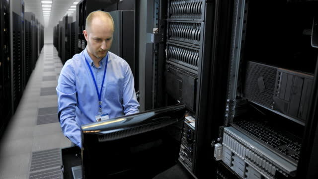 ld male it technician working on a omputer in the server room - network server stock videos & royalty-free footage
