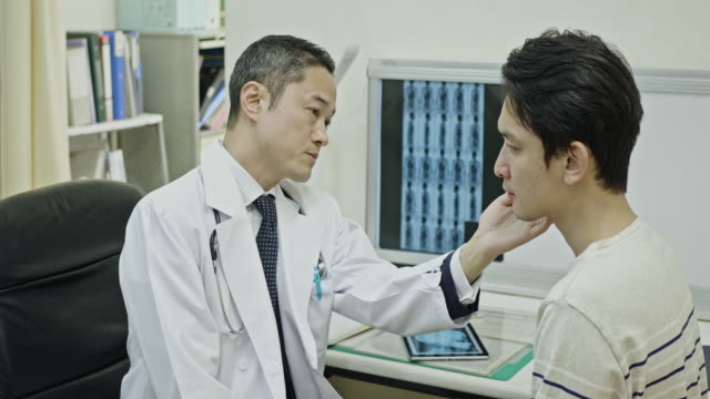Male Japanese Doctor examining patient's jaw in hospital