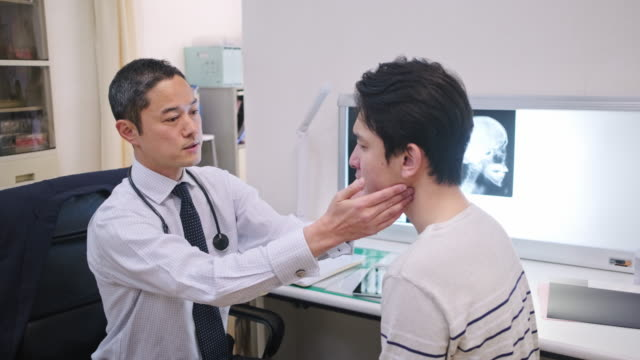 male japanese doctor examining young patient in hospital - physical therapy stock videos & royalty-free footage