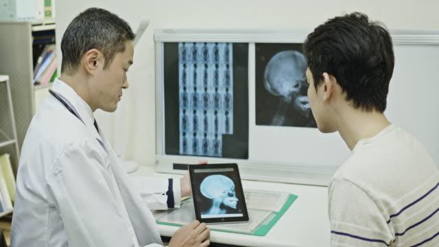 患者にx線画像を説明する日本人医師 - 健康診断点の映像素材/bロール