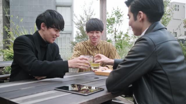 屋上庭園でお茶を楽しむ男性日本人の友達 - ヤングアダルト点の映像素材/bロール