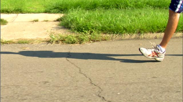 male jogger legs in baggy shorts & sneakers jogging on neighborhood road w/ sidewalk bg, long shadow in front of jogger. - ランニングショートパンツ点の映像素材/bロール