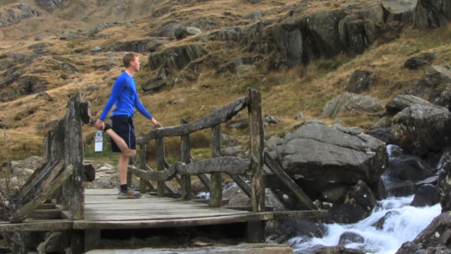 male jogger stretching on bridge; wales, uk - human muscle stock videos & royalty-free footage