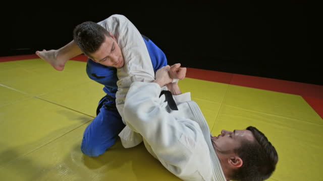 slo mo male judoist holding his opponent on the ground by clenching his arm - world sports championship stock videos & royalty-free footage