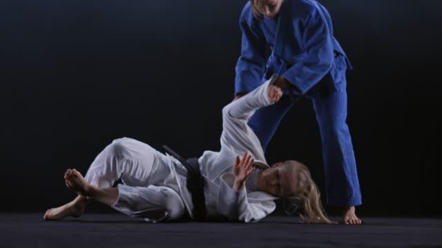 彼の背中と床の上に彼の相手を投げるし、彼女を下に保持する青い衣装で柔道家 ld オスの男の子 - 柔道点の映像素材/bロール