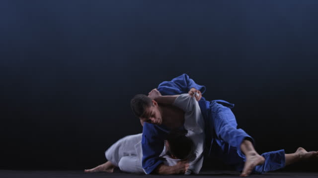 slo mo ld male judoka in blue outfit throwing his opponent over his back and on the floor - pinning stock videos & royalty-free footage