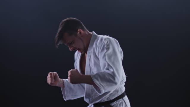 stockvideo's en b-roll-footage met slo mo mannelijke judoka in witte outfit gooien zijn tegenstander op de grond - worstelen
