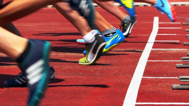 male junior sprinters starting from the starting block - atletico video stock e b–roll