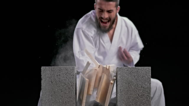 slo mo speed ramp ld male karateist breaking three wooden boards with a knife hand strike - plank stock videos & royalty-free footage