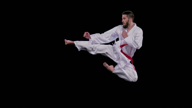 slo mo speed ramp male karateist doing a flying side kick - kicking stock videos & royalty-free footage