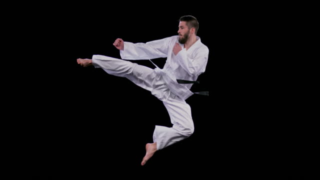 vídeos de stock e filmes b-roll de slo mo ld male karateist jumping into a flying side kick - artes marciais