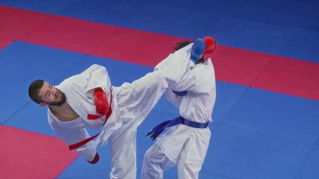 vidéos et rushes de slo mo karatéiste mâle coups de pied son adversaire dans la tête sur le tatami - karaté