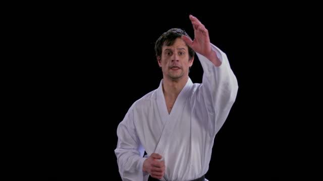 slo mo ld männlicher karateist mit schlägen in richtung kamera - karate stock-videos und b-roll-filmmaterial