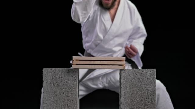 slo mo ld männliche karateka brechen drei holzbretter mit einem messer handschlag bewegen - karate stock-videos und b-roll-filmmaterial