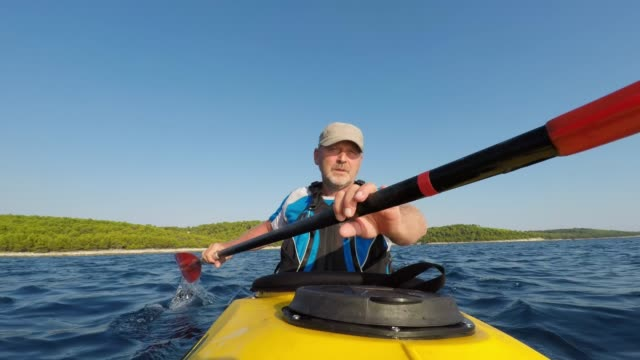 ld male kayaker paddling a yellow sea kayak in sunshine - canoe stock videos & royalty-free footage