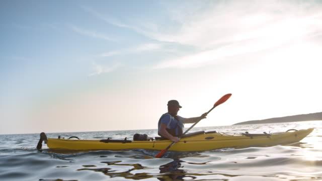 slo mo ts male kayaker paddling in his touring kayak in sunshine - kayaking stock videos & royalty-free footage