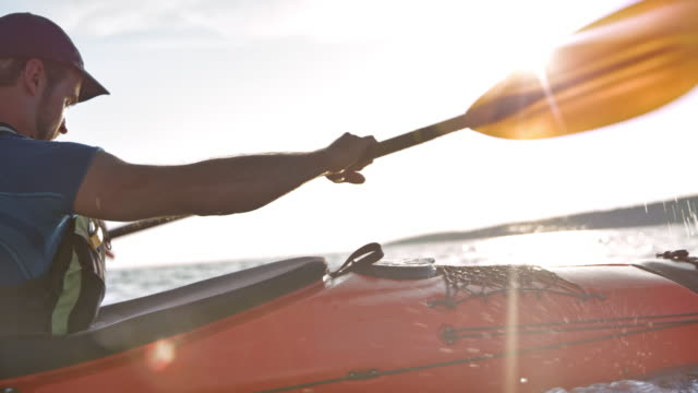 slo mo male kayaker paddling in sunshine - kayaking stock videos & royalty-free footage