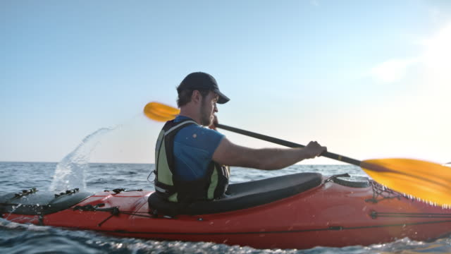 slo mo male kayaker riding across the calm sea in sunshine - water sport stock videos & royalty-free footage
