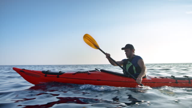 slo mo male kayaker riding his kayak across the sunny sea - red cap stock videos & royalty-free footage