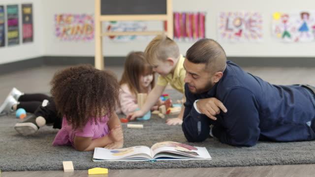 männliche kindergarten-lehrer lesen buch zu schüler - leidenschaft stock-videos und b-roll-filmmaterial
