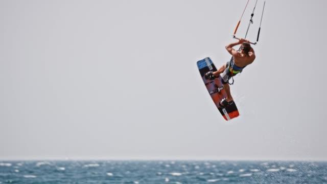 vídeos y material grabado en eventos de stock de kiteboarder slo mo hombre saltando en el aire y haciendo un gancho agarrador - vestido parcialmente
