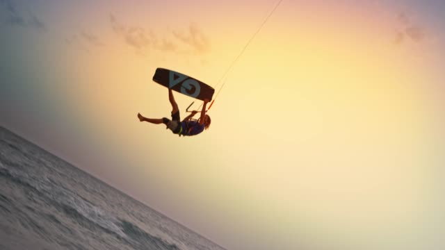 SLO MO Male kiteboarder jumping into the air as the sun is setting