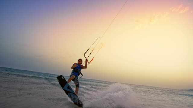 SLO MO Male kiteboarder jumping into the air, doing a grab and looking into the camera at sunset