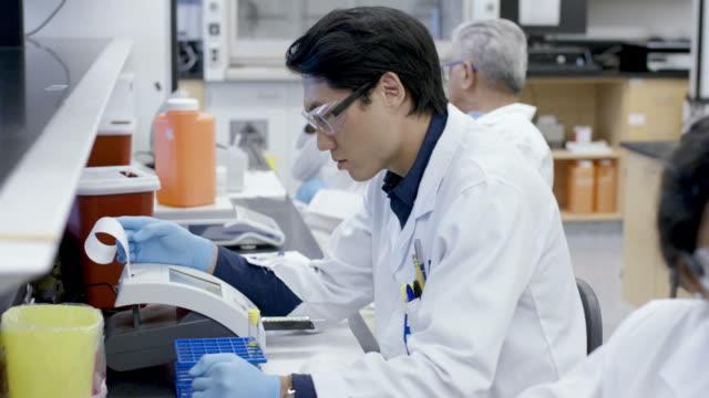 小さな器械からの結果を分析する男性の実験室の技術者 - 韓国人点の映像素材/bロール