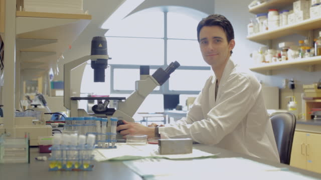 vidéos et rushes de ms pan male laboratory technician looking into microscope in cancer research healthcare medicine  industry dna sequencing  laboratory / vancouver, bc, canada   - blouse de laborantin
