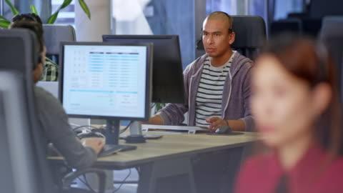 manlig latinamerikansk callcenter kundtjänstrepresentant som arbetar vid sitt skrivbord i call center - hörlurar bildbanksvideor och videomaterial från bakom kulisserna
