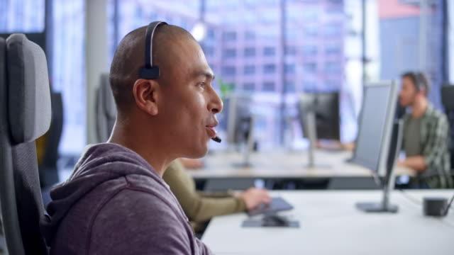 vídeos y material grabado en eventos de stock de ds male agente de centro de llamadas latinoamericano que proporciona servicio al cliente en su estación de trabajo - call center latin