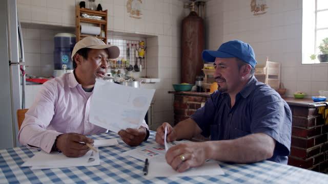 stockvideo's en b-roll-footage met mannelijke latijns-amerikaanse landbouwers die zaken bespreken terwijl het bekijken van documenten bij een landelijk huis - latijns amerika