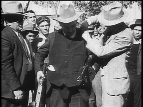 b/w 1934 male law enforcement officer pursuing dillinger with bulletproof vest 2 tommy guns / tucson - john dillinger stock-videos und b-roll-filmmaterial