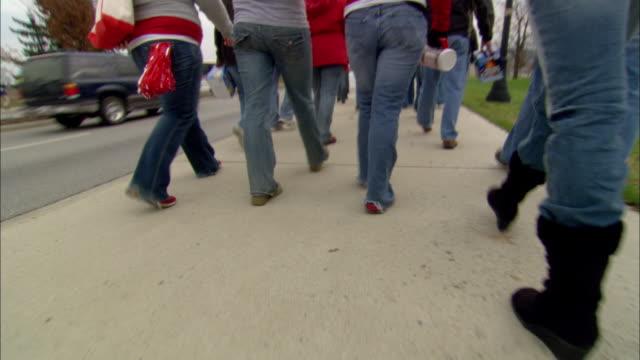 male legs in baggy shorts & tennis shoes jogging sideways, more hop than jog, on sidewalk. - ランニングショートパンツ点の映像素材/bロール
