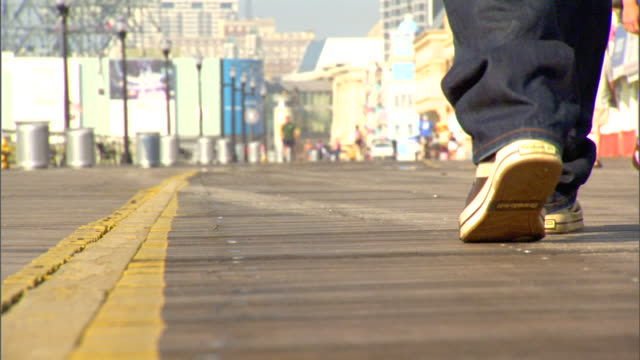 male legs in jeans & tennis shoes walking on walkway alone. healthy lifestyle, beach, beachfront, exercise, relaxing. - baggy jeans stock videos & royalty-free footage