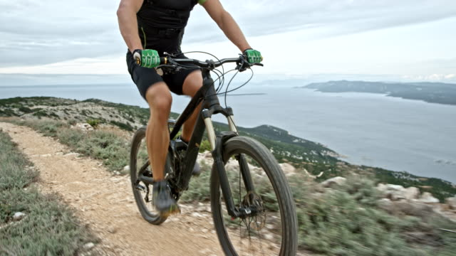 Male legs pushing the bike pedals while riding on a mountain ridge above the sea