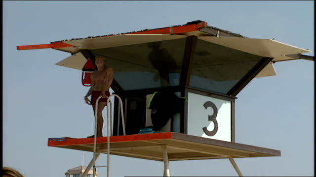 male life guard standing on top of guard tower in huntington ca - cabina del guardaspiaggia video stock e b–roll