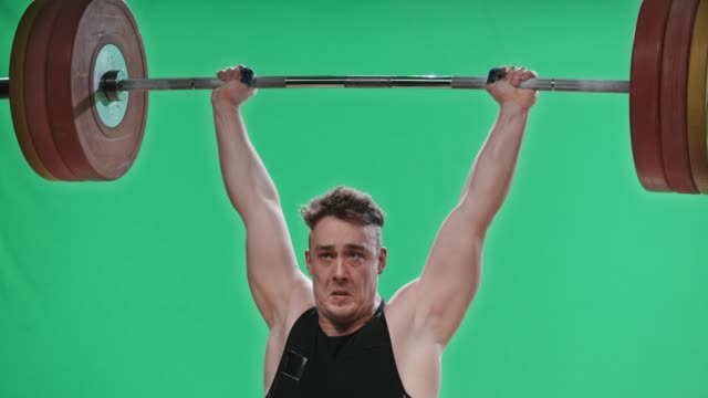 slo mo tu male lifter raising the barbell above his head - weight training stock videos & royalty-free footage